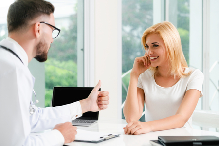 Male doctor is talking to female patient in hospital office. Healthcare and medical service. Stock Photo