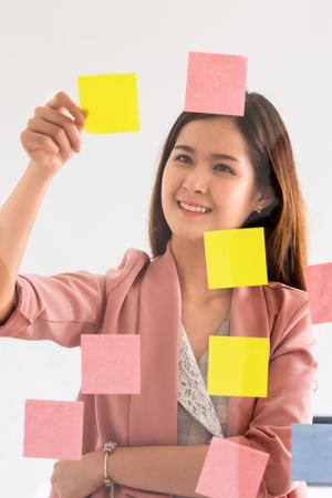 Glückliche Geschäftsfrau, die kreative Ideen mit Haftnotizen an der Glaswand im Büro denkt. Arbeitsplanung und Bildungskonzept
