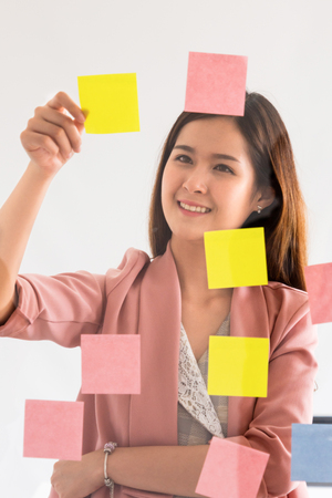 Happy businesswoman thinking creative ideas with sticky notes on glass wall at the office. Work planning and education concept