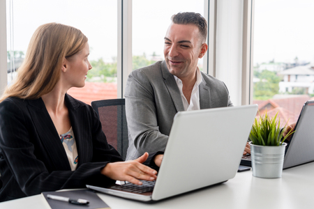 Businessman executive is in meeting discussion with a businesswoman worker in modern workplace office. People corporate business team concept. Banque d'images