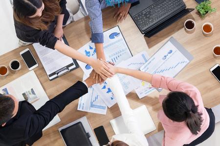 Zakenlieden en zakenvrouwen slaan de handen ineen in groepsbijeenkomst in multiculturele kantoorruimte die teamwerk, ondersteuning en eenheid in het bedrijfsleven laat zien. Diversiteit werkplek en zakelijke mensen werken concept. Stockfoto