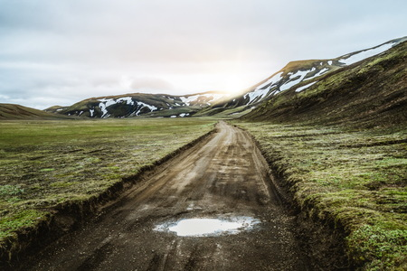 Beautiful Landmanalaugar gravel dust road way on highland of Iceland, Europe. Muddy tough terrain for extreme 4WD 4x4 vehicle. Landmanalaugar landscape is famous for nature trekking and hiking. Banco de Imagens