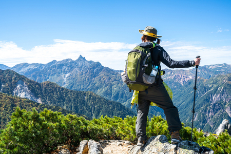 Epic adventure of hiker do trekking activity in mountain of Northern Japan Alps, Nagano, Japan, with panoramic nature mountain range landscape. Motivation leisure sport and discovery travel concept. Banque d'images