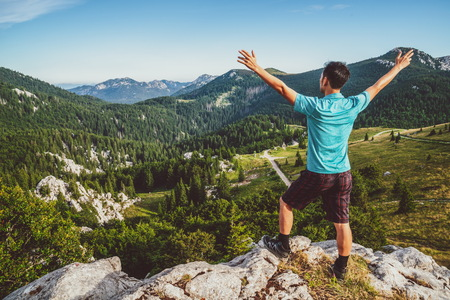 Young man traveler and explorer travels in the forest and mountain nature landscape hiking across Zavizan Gora in Croatia. Reklamní fotografie