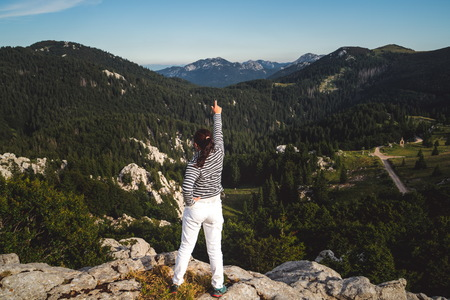 Young woman traveler and explorer travels in the forest and mountain nature landscape hiking across Zavizan Gora in Croatia.