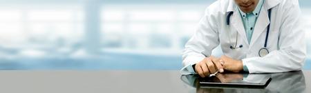 Mannelijke arts zittend aan tafel met tablet pc in ziekenhuis kantoor. Medisch zorgpersoneel en doktersdienst.