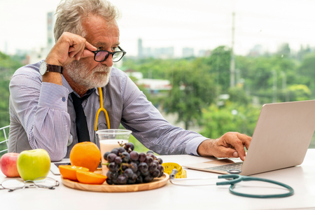 Senior male nutritionist doctor working with laptop computer on table in the hospital office. Dieting and healthy eating concept. Stock Photo