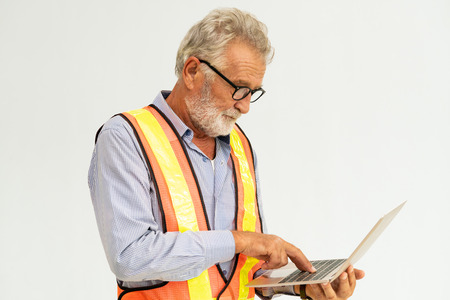 Experienced senior foreman or engineer using laptop computer standing against white background. Construction and engineering concept.