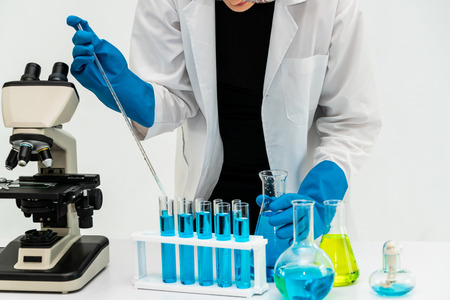 Young woman scientist working in chemical laboratory and examining biochemistry lab sample. Science technology medicine research and development study concept.