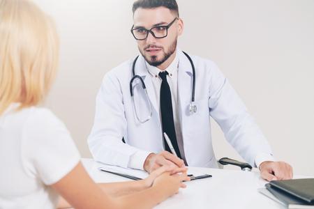 Mannelijke arts praat met vrouwelijke patiënt in het ziekenhuiskantoor. Gezondheidszorg en medische dienst.