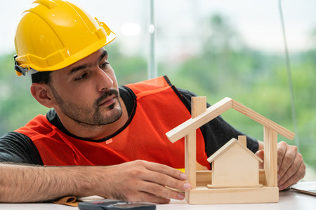 Young man construction worker or engineer working at desk with designer equipment to make interior design at workplace. Real estate business and civil engineering concept. Banco de Imagens - 121491146