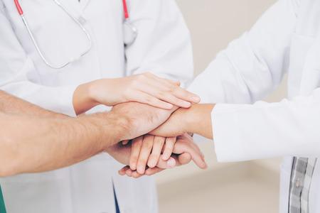 Trabajo en equipo de servicios médicos: el médico, el cirujano y la enfermera se dan la mano.