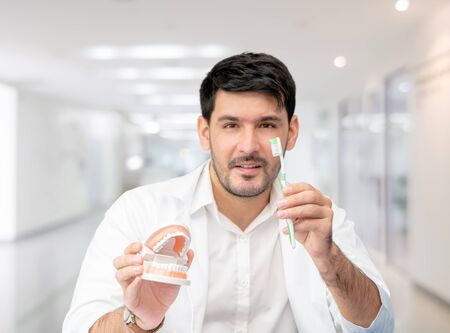 Young male dentist showing toothbrush and denture in dental clinic. Selective focus at the toothbrush. Banque d'images - 129249525