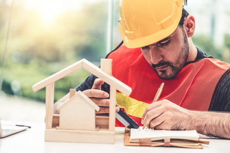 Young man construction worker or engineer working at desk with designer equipment to make interior design at workplace. Real estate business and civil engineering concept.