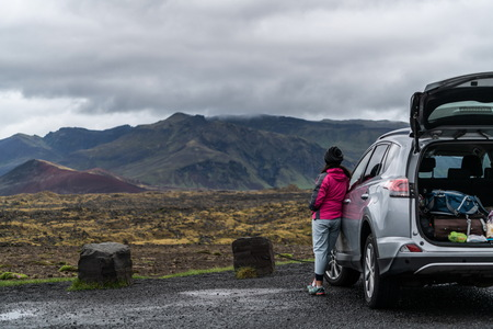 Woman tourist travel by SUV car for road trip in Iceland. The traveler parking the car and enjoy beautiful scenery of mountain landscape in the background. Discovery and exploration.
