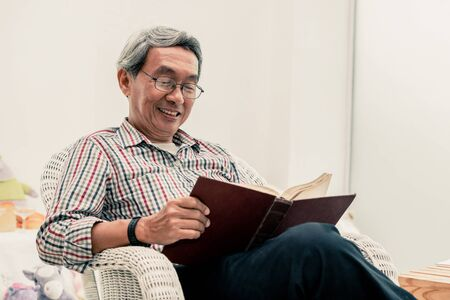 Happy senior Asian man reading book on the chair in living room at home. Retirement lifestyle and aging society concept.