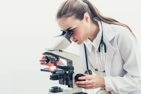 Young female doctor working using microscope in hospital laboratory. Medical and medicine technology research and development concept.