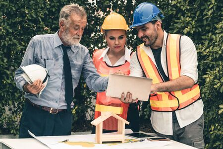 Engineer, architect and business man working on the engineering project at construction site. House building concept.