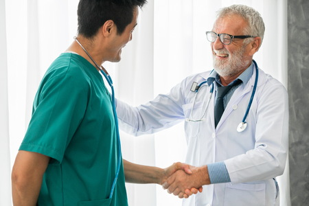 Senior male doctor working with another doctor in hospital. Concept of medical healthcare and doctor staff education.