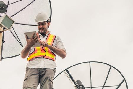 Professioneller Techniker oder Ingenieur, der auf dem Dach des Gebäudes steht und mit einer Satellitenschüssel arbeitet. Konzept des Reparaturinstallationsdienstes und der Telekommunikation.