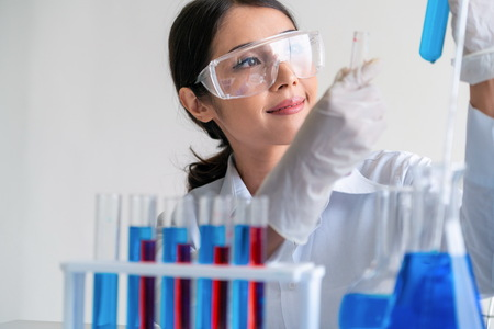 Woman scientist working in laboratory and examining biochemistry sample in test tube. Science technology research and development study concept. Stock fotó