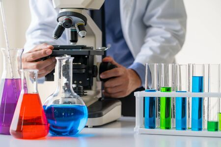 Man scientist working in pharmaceutical laboratory and examining biochemistry sample in microscope. Science technology medicine research and development study concept.