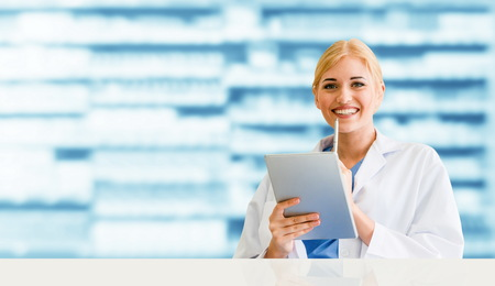 Pharmacist using tablet computer at the pharmacy. Medical healthcare and pharmaceutical staff service. Banque d'images