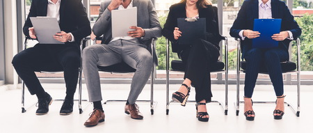 Businesswomen and businessmen holding resume CV folder while waiting on chairs in office for job interview. Corporate business and human resources concept. Stock fotó