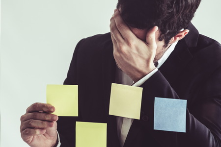 Serious businessman feels disappointed while looking at sticky note on the windows in the office. Bankruptcy and failure concept. Stock Photo
