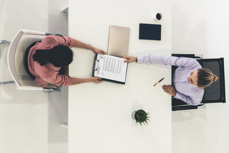 Two young business women in meeting at office table for job application and business agreement. Recruitment and human resources concept.
