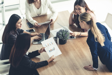 Femme d'affaires en réunion de groupe avec d'autres collègues femmes d'affaires dans un bureau moderne avec ordinateur portable et documents sur table. Concept d'équipe de travail d'entreprise de personnes.