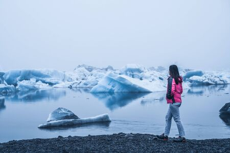 Woman traveler travels to Jokulsarlon beautiful glacial lagoon in Iceland. Jokulsarlon is a famous destination in Vatnajokull National Park, southeast Iceland, Europe. Cold winter ice nature. Stock fotó