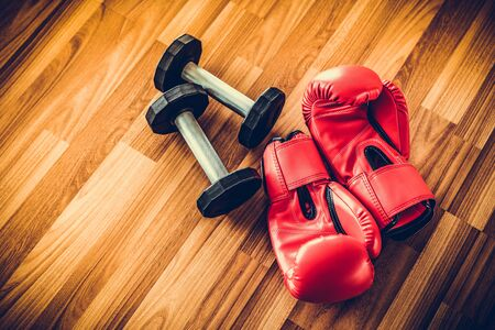Red boxing gloves on wood background. Sport and healthy lifestyle concept.