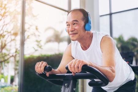 Starszy mężczyzna ćwiczenia na maszynie rowerowej w centrum fitness. Dojrzały zdrowy styl życia.