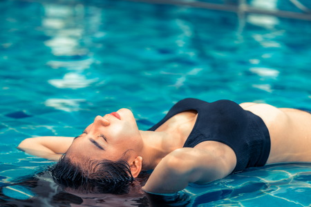Young relaxed woman at swimming pool in summer in luxury beach resort. Travel and lifestyle.