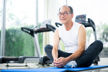 Senior man do body stretching in fitness center. Healthy lifestyle. Stockfoto