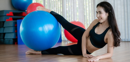 Beautiful young woman in fitness center doing pilates exercise with fitness ball. Healthy lifestyle concept.