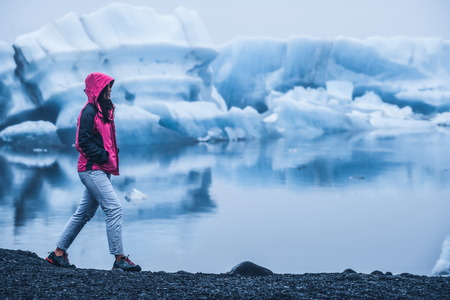 Woman traveler travels to Jokulsarlon beautiful glacial lagoon in Iceland. Jokulsarlon is a famous destination in Vatnajokull National Park, southeast Iceland, Europe. Cold winter ice nature. Stock Photo