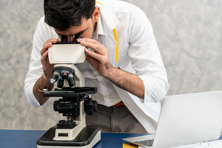 Young male doctor working using microscope in hospital laboratory. Medical and medicine technology research and development concept.