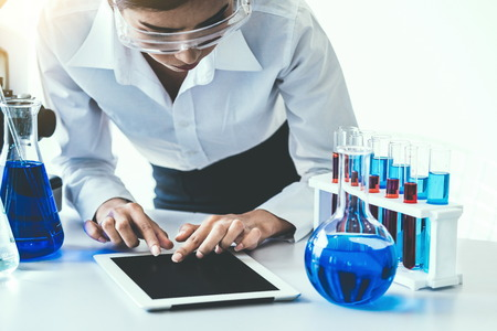 Woman scientist working in laboratory and examining biochemistry sample in test tube. Science technology research and development study concept. Stockfoto