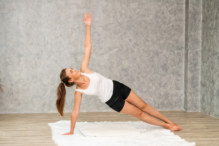 Young beautiful woman do yoga exercise on carpet at home living room. Healthy lifestyle and relaxation. Stock Photo