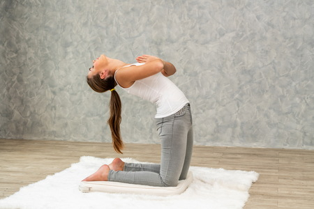 Young beautiful woman do yoga exercise on carpet at home living room. Healthy lifestyle and relaxation. 版權商用圖片