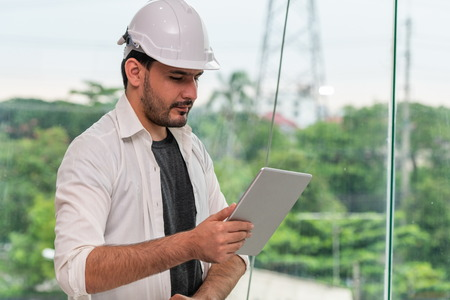 Young man architect or engineer working with tablet computer to make interior design at workplace. Real estate business and civil engineering concept. Stock Photo