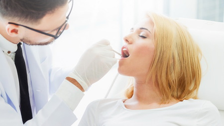 Young handsome dentist examining teeth of happy woman patient sitting on dentist chair in dental clinic. Dentistry care concept.