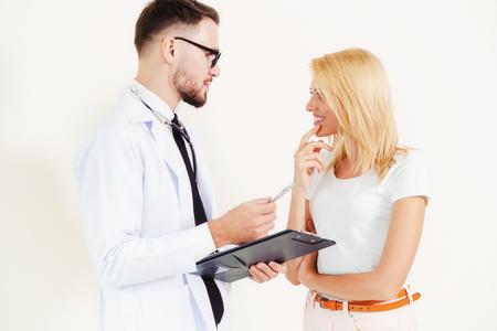 Il medico maschio e il paziente femminile con i documenti della cartella clinica dei pazienti stanno conversando in ospedale. Assistenza sanitaria e servizio medico.