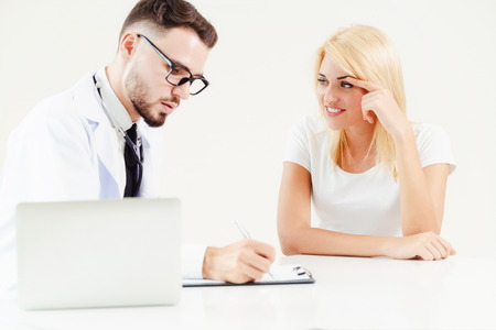 Male doctor talks to female patient in hospital office while writing on the patients health record on the table. Healthcare and medical service. Stock Photo