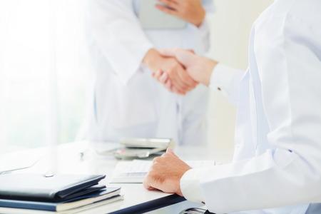 Arzt im Krankenhaus, der einem anderen Arzt den Handschlag gibt und den Erfolg und die Teamarbeit des professionellen Gesundheitspersonals zeigt.