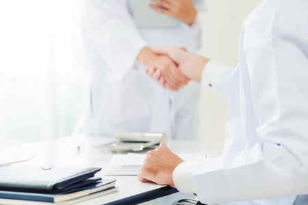 Dottore in ospedale che dà la stretta di mano a un altro medico che mostra il successo e il lavoro di squadra del personale sanitario professionale.