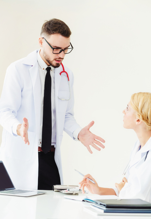 Young female doctor at hospital office having conversation talking with another male doctor standing beside the table. Concept of medical healthcare professional team.