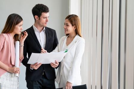 El hombre de negocios está en la discusión de la reunión con las empresarias del colega en la oficina del lugar de trabajo moderno. Concepto de equipo de negocios corporativos de personas. Foto de archivo